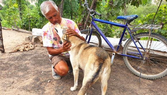 'Manolo' entregando amor a uno de sus fieles acompañantes. Detrás se ubica el terreno en donde siembra diferentes frutas. Foto: Bryan Ortiz