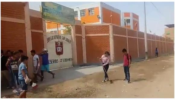 Niños hacen limpieza afuera de su colegio