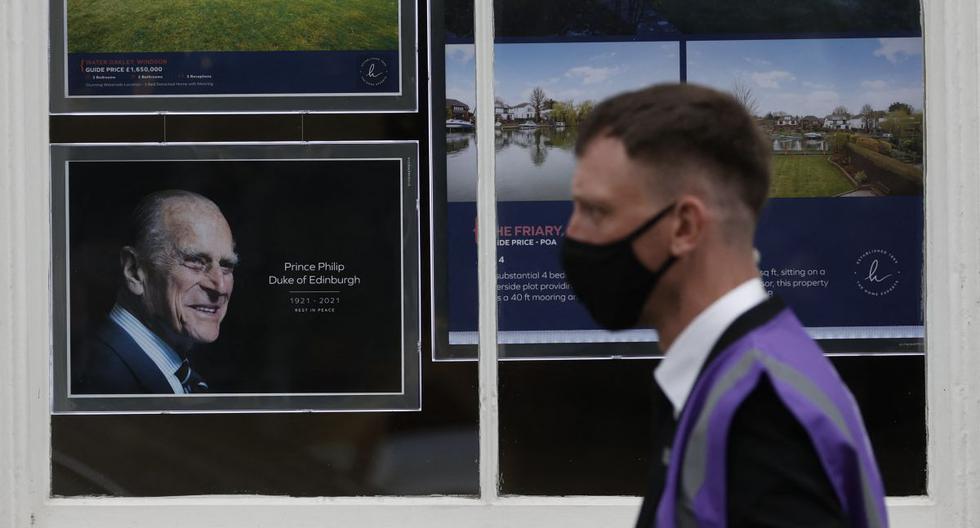 Un hombre pasa junto a una foto del príncipe Felipe, duque de Edimburgo, que se muestra en la ventana de una agencia inmobiliaria en Windsor, al oeste de Londres, el 16 de abril de 2021. (Adrian DENNIS / AFP).