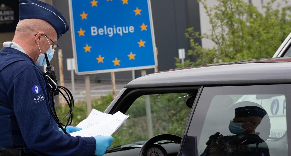 Un oficial de policía belga controla los documentos de una persona en un automóvil en la frontera entre Bélgica y Francia durante una patrulla policial en Quevy, haciendo cumplir las reglas de distanciamiento social. (BENOIT DOPPAGNE / AFP)