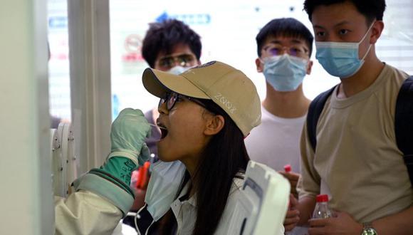 Se toma una muestra de hisopo de una mujer para ser examinada por el coronavirus en un hospital en Beijing el 2 de agosto de 2021, en medio del brote de coronavirus más extendido del país en meses. (Foto de Noel Celis / AFP).