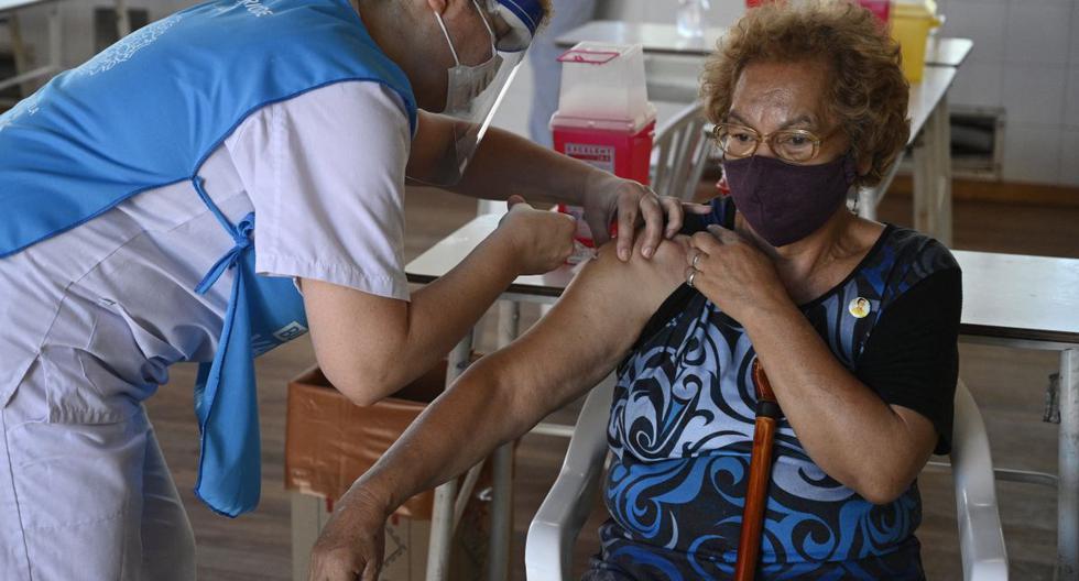 Un trabajador de salud aplica una dosis de la vacuna Sputnik V contra COVID-19 a una anciana en Ezeiza, a las afueras de Buenos Aires (Argentina). (JUAN MABROMATA / AFP).