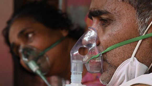 Pacientes de coronavirus respiran con la ayuda del oxígeno proporcionado por un Gurdwara, un lugar de culto para los sijs, en Ghaziabad, India, el 1 de mayo de 2021. (Foto de Sajjad HUSSAIN / AFP).