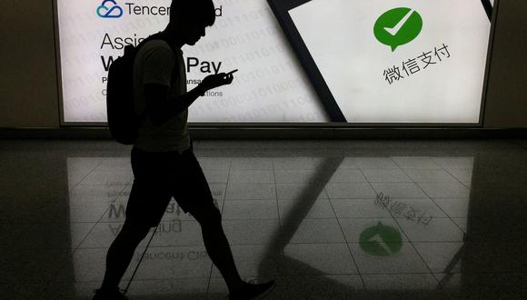 Imagen referencial. Un hombre es visto caminando con su teléfono frente a un anuncio de la plataforma de redes sociales WeChat. Foto del 21 de agosto de 2017. (AFP / RICHARD A. BROOKS).
