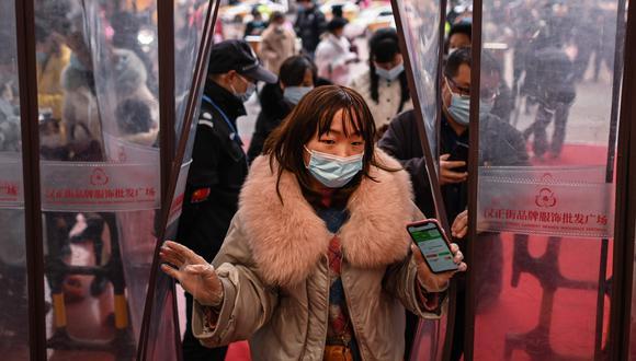 Una mujer que usa una mascarilla como medida preventiva contra el coronavirus ingresa a un centro comercial después de mostrar su código de salud en Wuhan, provincia central de Hubei en China. (Foto: HÉCTOR RETAMAL / AFP)