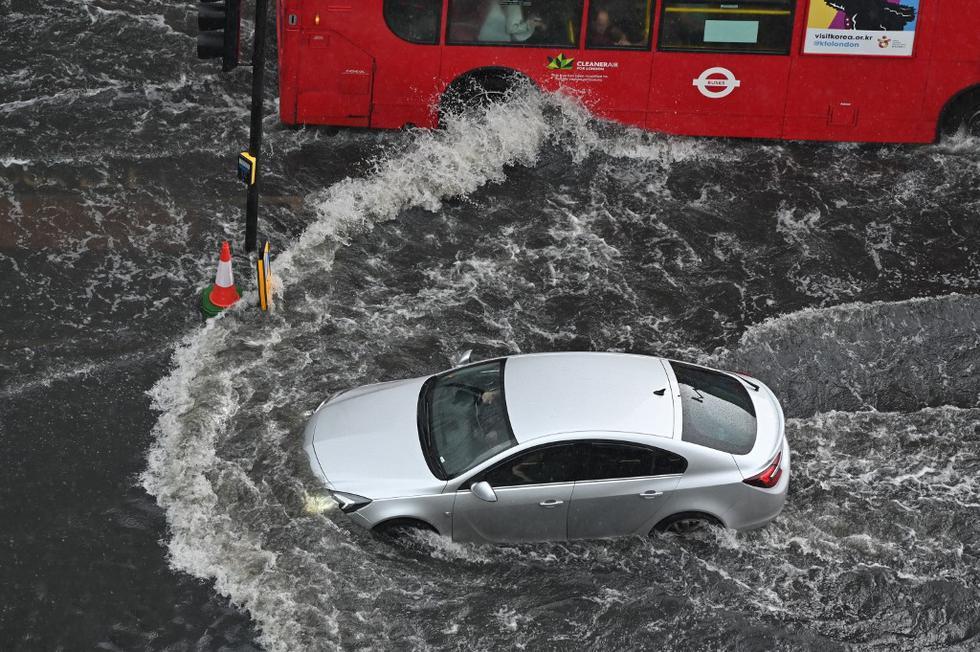 Coches y los característicos autobuses rojos quedaron bloqueados y no podían avanzar en zonas de la capital británica, según imágenes publicadas en redes sociales. En la imagen se aprecia un automóvil y un autobús típico londinense atravesando aguas profundas en una carretera inundada en el distrito de The Nine Elms. (Texto: AFP / Foto de JUSTIN TALLIS / AFP)