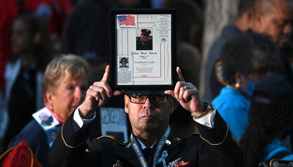 Un bombero sostiene la imagen de una víctima del 11 de septiembre mientras la gente asiste a una ceremonia que conmemora el 20 aniversario de los ataques del 11 de septiembre en el World Trade Center, en Nueva York. (Foto: Jim WATSON / AFP)