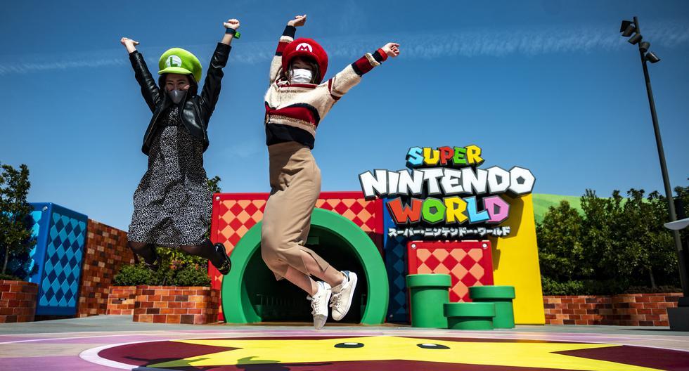 En esta foto tomada el 17 de marzo de 2021, los fanáticos de Universal Studio Japan posan en la entrada del Super Nintendo World, durante una vista previa para los medios del parque temático en Osaka. (Philip FONG / AFP).