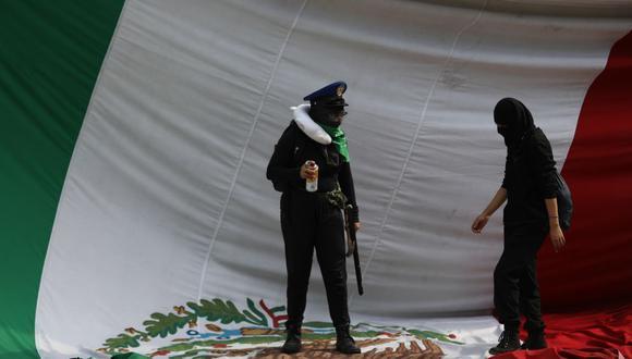 Imagen referencial. Activistas caminan sobre una bandera mexicana en el Instituto Politécnico Nacional, en Ciudad de México (México). (EFE/Sáshenka Guitiérrez).