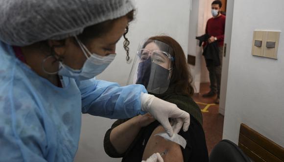 Una mujer recibe una dosis de la vacuna Pfizer-BioNtech en Montevideo, mientras Uruguay lanza su campaña para administrar dosis de refuerzo a personas completamente inmunizadas con CoronaVac. (Foto: Eitan ABRAMOVICH / AFP)