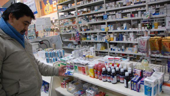 Un hombre mirando qué medicinas comprar en una farmacia.