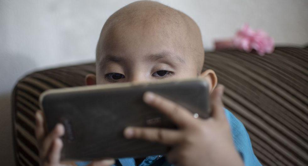 Cristal Flores, diagnosticado con cáncer, ve dibujos animados en un teléfono celular en la casa de un pariente, en Cuautitlán. (AFP).