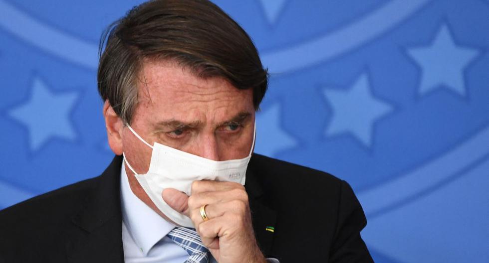 El presidente de Brasil, Jair Bolsonaro, tose durante la firma de la ley que autoriza a los estados, municipios y al sector privado a comprar vacunas contra el coronavirus COVID-19, el 10 de marzo de 2021. (Foto de EVARISTO SA / AFP).