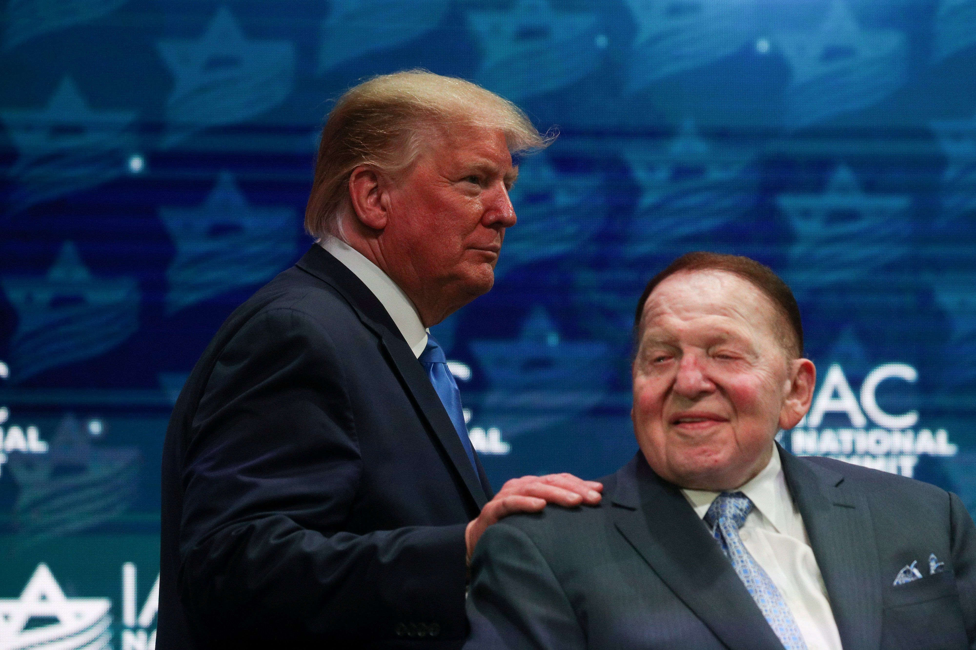 El presidente de Estados Unidos, Donald Trump, saluda a Sheldon Adelson mientras sube al escenario en la Cumbre Nacional del Consejo Estadounidense Israelí en Hollywood, Florida, el 7 de diciembre de 2019. (REUTERS/Loren Elliott).