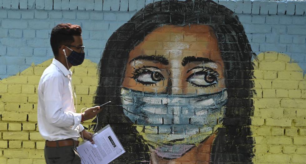 Un hombre pasa junto a un mural sobre el coronavirus Covid-19 en Nueva Delhi el 7 de noviembre de 2020 (Foto de Sajjad HUSSAIN / AFP).