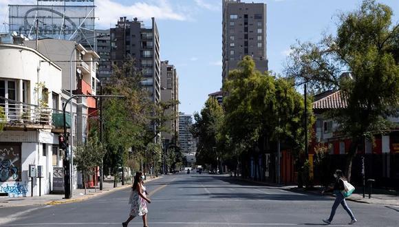 Dos mujeres caminan por una avenida semi vacía en Santiago de Chile. La ciudad se encuentra en una nueva jornada de cuarentena obligatoria decretada ante el avance del coronavirus. (EFE/ Alberto Valdés).