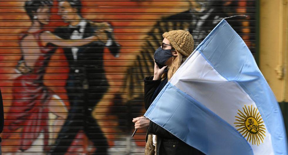 Una mujer camina con la bandera de Argentina en protesta contra el Presidente Alberto Fernández. (Fotos: JUAN MABROMATA / AFP)