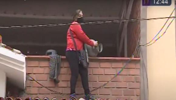 La vecina Sara Salas coge un balón de gas para evitar un desalojo en su casa ubicada en la urbanización La Modesta, en Surco. (Captura. Canal N)