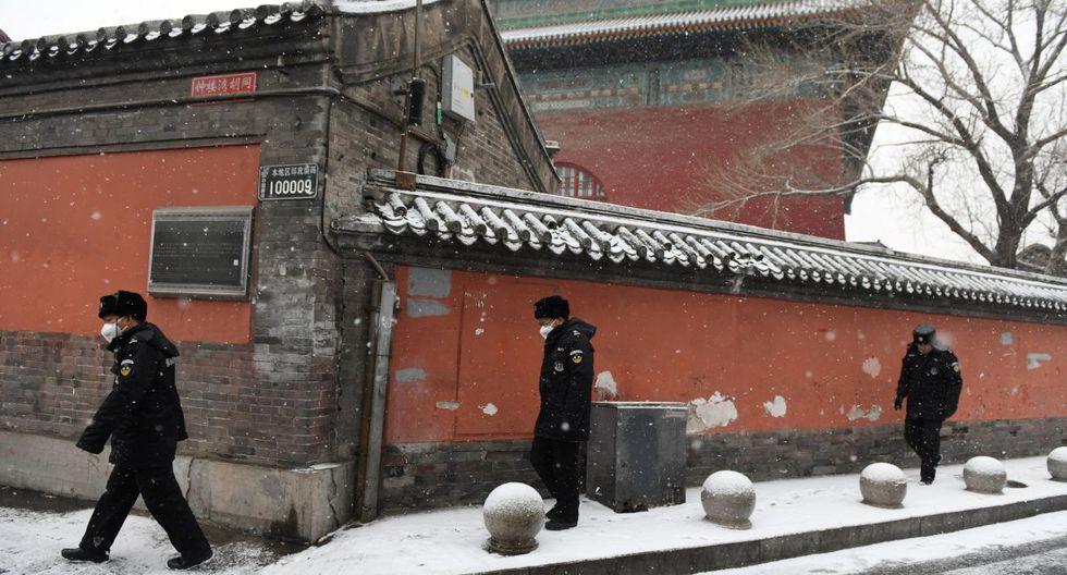 Agentes de seguridad caminan en las calles con sus mascarillas para evitar la propagación de la enfermedad. (AFP).
