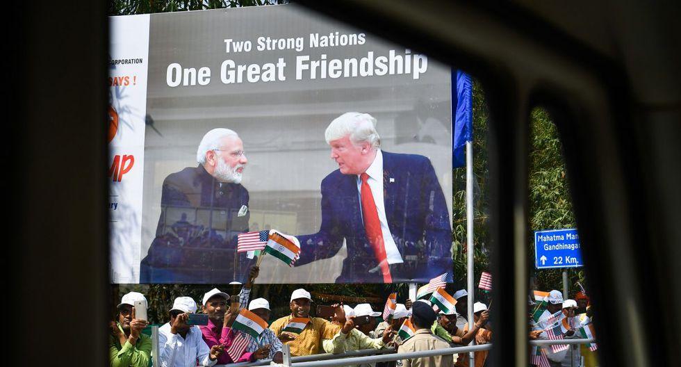 La gente agita las banderas de los EE. UU. y la India mientras una caravana que transporta al presidente de los Estados Unidos, Donald Trump, pasa por Ahmedabad. (AFP)