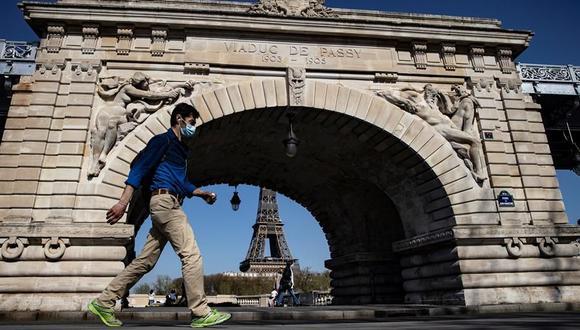 Un peatón que usa mascarilla para protegerse del coronavirus camina por el puente Bir Hakeim, cerca de la Torre Eiffel. Francia atraviesa una tercera cuarentena. (Foto: EFE)