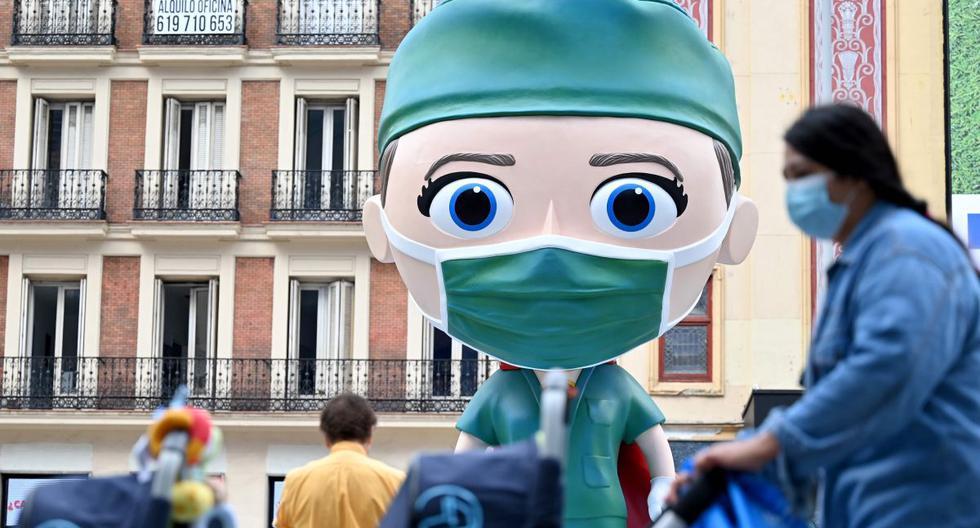 Personas con mascarillas caminan el 24 de setiembre de 2020 junto a una estatua de 6 metros de altura en Madrid, España. (AFP / Gabriel BOUYS).