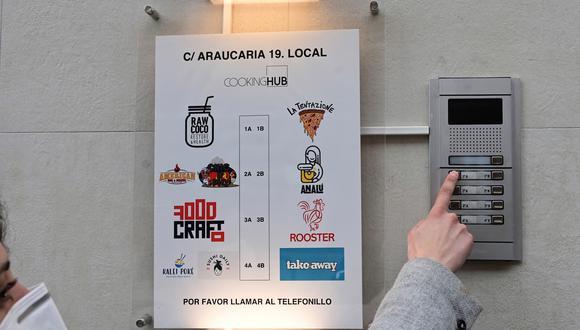 """Una mujer llama al telefonillo de una de las llamadas """"cocinas fantasmas"""" situada en el madrileño barrio de Tetuán. La pandemia ha traído consigo en ciudades como Madrid la proliferación de las 'cocinas fantasma', dedicadas exclusivamente a la comida a domicilio, un negocio reciente con límites difusos que provoca además quejas de vecinos. (Foto: EFE/Víctor Lerena)"""