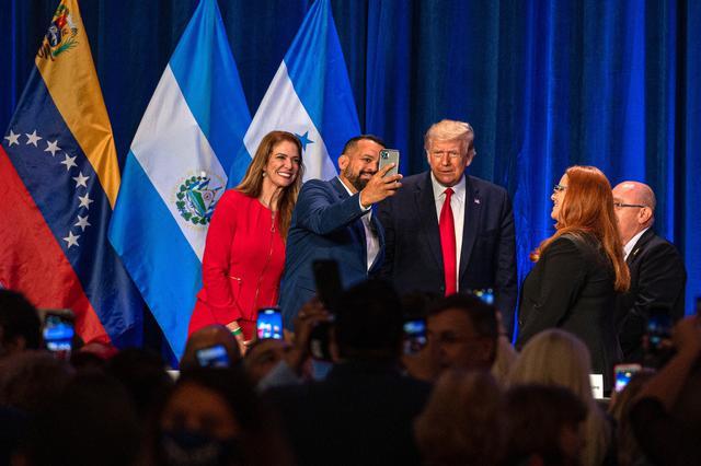 """La experta en bienes raíces, Karla Salvatierra (izquierda), y el banquero puertorriqueño Hiram Turul (2 izquierda), se toman una fotografía con el mandatario de los Estados Unidos, Donald J. Trump (centro), frente a la cubana Carolina Ferreiro (2 derecha), de Pharma Natural, y el presidente de Americas Community Cinter, el colombiano Fabio Andrade (derecha), durante el encuentro de """"Latinos por Trump"""" este viernes en Doral, ciudad aledaña a Miami, Florida. (EFE/Giorgio Viera)."""