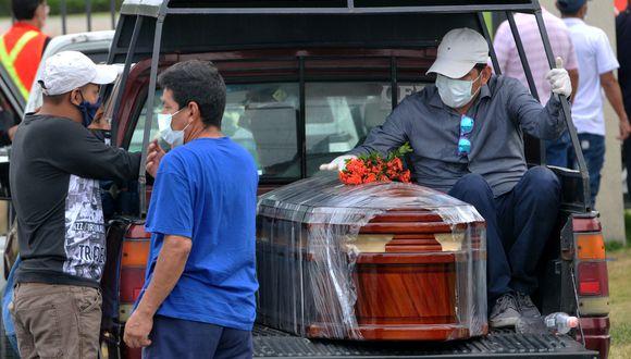 Familiares de una víctima del nuevo coronavirus COVID-19, llegan con el ataúd de su ser querido enfermo al cementerio de Paque de la Paz en Guayaquil, Ecuador. (Foto: AFP/José Sánchez)