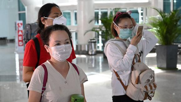 Chinese tourists wearing facemasks arrive Ngurah Rai airport in Denpasar on February 8, 2020. The new coronavirus that emerged in a Chinese market at the end of last year has killed more than 700 people and spread around the world. / AFP / SONNY TUMBELAKA