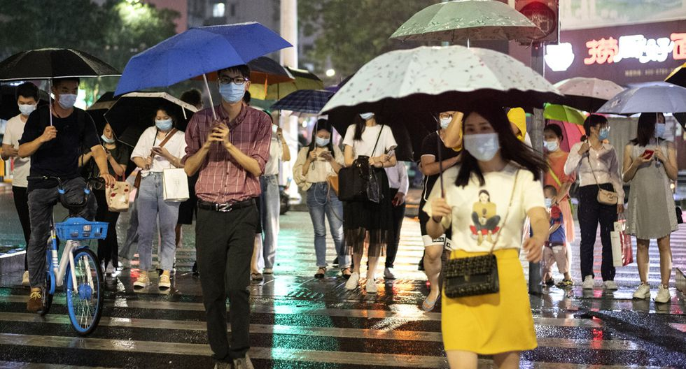 Las personas que usan mascarilla protectora caminan bajo sus paraguas mientras llueve en Shenzhen, en la provincia sureña china de Guangdong, mientras la nación avanza lentamente hacia la normalidad después de la nueva pandemia de coronavirus, COVID-19. (Foto: AFP/NOEL CELIS)