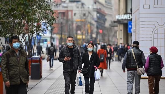 En esta foto tomada el 5 de marzo de 2021, una pareja camina por una calle comercial en Shanghai. (Foto: AFP / Hector RETAMAL)