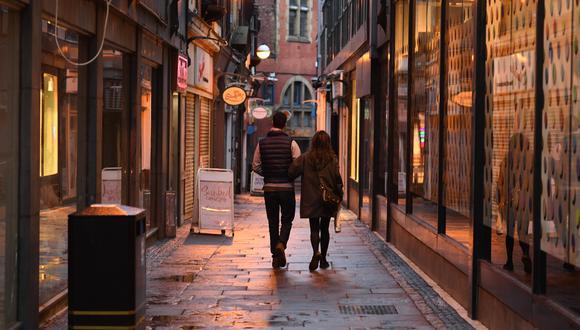 Una pareja pasa frente a tiendas cerradas en el centro de Sheffield, en el norte de Inglaterra, el 21 de octubre de 2020, antes de nuevas medidas para frenar el coronavirus. (Foto de Oli SCARFF / AFP).