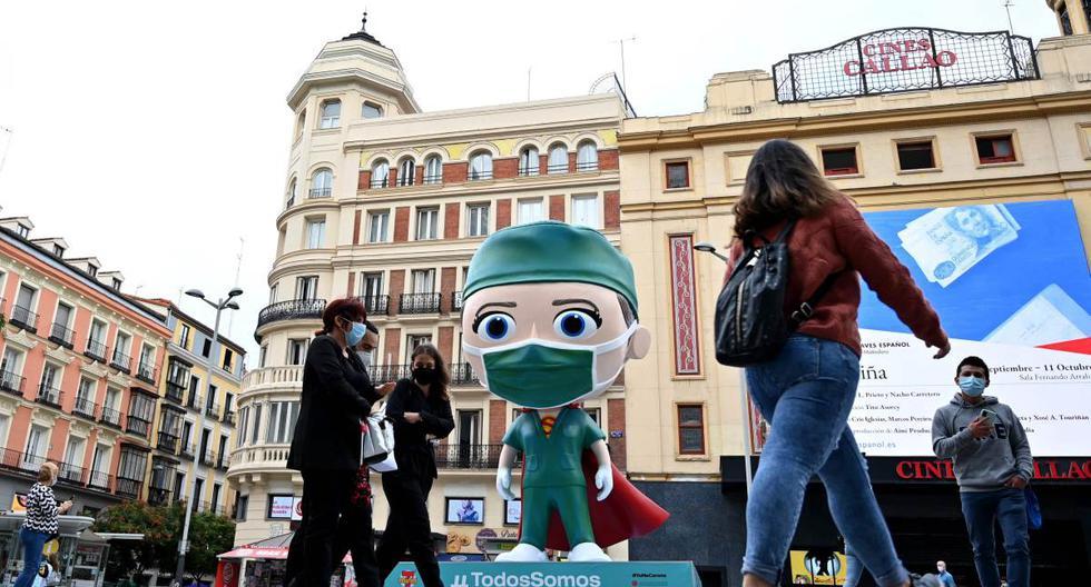 """Personas con mascarillas caminan junto a una estatua de 6 metros de un """"Súper trabajador de la salud"""" instalado en Madrid. La región vive una preocupante situación por la pandemia de coronavirus. (AFP / Gabriel BOUYS)."""