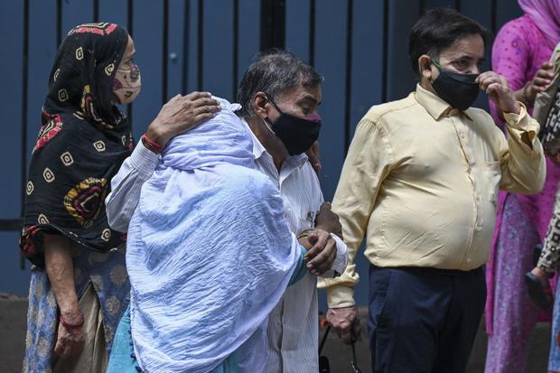 Los familiares lloran mientras esperan recibir el cuerpo de su ser querido, que murió debido al coronavirus, en una morgue en Nueva Delhi (India), el 21 de mayo de 2021. (Prakash SINGH / AFP).