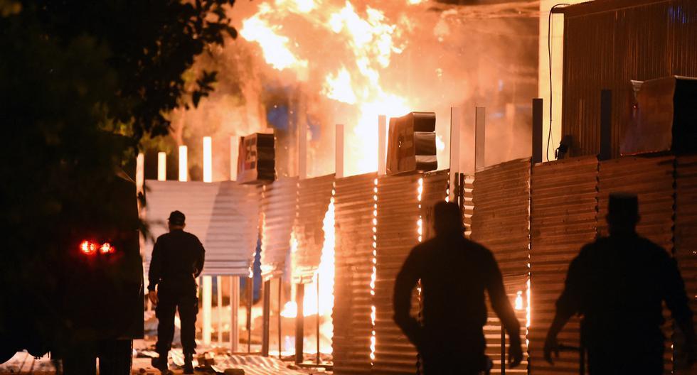 Policías son vistos cerca de un incendio provocado por manifestantes en la sede del Ministerio de Comercio. (NORBERTO DUARTE / AFP).
