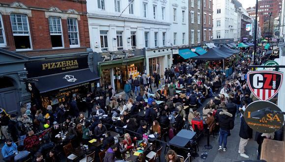 Coronavirus: La gente se sienta en mesas al aire libre para comer y beber en bares y restaurantes reabiertos en Londres, Reino Unido, el 16 de abril de 2021. (Foto de Niklas HALLE'N / AFP).