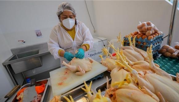 Una vendedora sujetando un pollo, animal que vende para el consumo humano. | Foto: Produce.