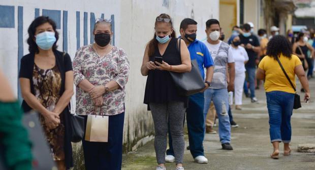 Varias personas acuden a un centro de votación en el colegio Calicuchima con doble mascarilla y un visor para protegerse del COVID-19, hoy, en Guayaquil (Ecuador). (EFE/ Marcos Pin).