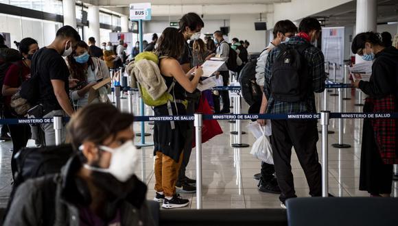 Los pasajeros chilenos repatriados llenan un formulario de declaración sanitaria a su llegada al Aeropuerto Internacional de Santiago el 8 de mayo de 2020. (Martin BERNETTI / AFP).