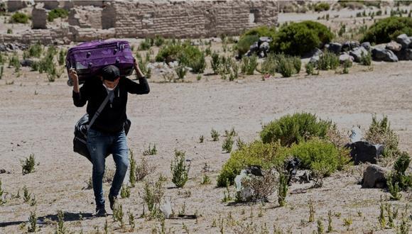 Venezolano cargando su mochila para ingresar a Chile. | Foto: AFP