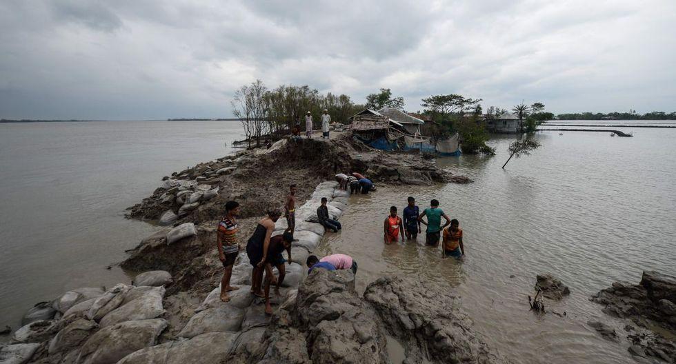 Voluntarios y residentes trabajan para reparar una presa dañada tras la llegada del ciclón Amphan en Burigoalini, Bangladesh, el 21 de mayo de 2020. Al menos 84 personas murieron cuando el ciclón más feroz que golpeó partes de Bangladesh y el este de la India este siglo envió árboles volando y casas aplastadas, con millones se apiñaron en refugios a pesar del riesgo de coronavirus. (AFP / Munir uz Zaman)