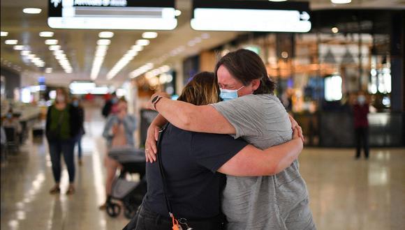 Una madre (derecha) abraza a su hija a su llegada desde Nueva Zelanda al Aeropuerto Internacional de Sydney este 19 de abril de 2021, cuando Australia y Nueva Zelanda abrieron una burbuja de viajes sin cuarentena a través de Tasmania. (Foto de SAEED KHAN / AFP)