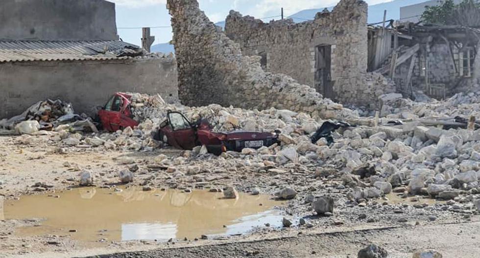 La gente pasa frente a una casa destruida después del terremoto en la isla de Samos (Grecia), el 30 de octubre de 2020. (AFP / Eurokinissi / STR).