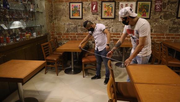 MEX3354. CIUDAD DE MÉXICO (MÉXICO), 29/06/2020. Dos empleados de un restaurante acomodan el mobiliario este lunes, en los trabajos de remodelación para la reapertura de negocios en la Ciudad de México (México). Los restaurantes se preparan en la nueva normalidad con estrictas medidas de higiene y con la capacidad de el 30 por ciento de aforo de clientes.EFE/Sáshenka Gutiérrez