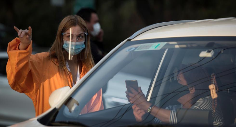Imagen referencial. Una pareja pasa un control sanitario a la entrada del autocine de la comuna las Condes en Santiago. (EFE/Alberto Valdés).