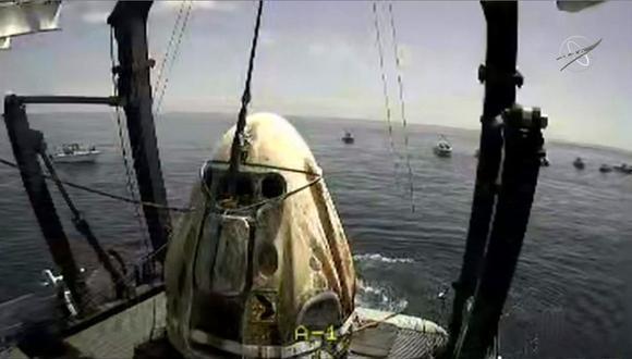 En esta captura de video de la NASA se aprecia al Crew Dragon Endeavor poco después de ser izada en el Golfo de México. Los astronautas que viajaban en la nave, Behnken y Hurley, regresaron a la tierra después de pasar 64 días en el espacio. (NASA / AFP)