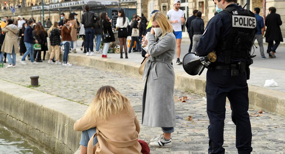Un policía francés habla con mujeres que disfrutan de un día soleado a orillas del río Sena en medio de la nueva pandemia de coronavirus en París, el 20 de febrero de 2021. (Bertrand GUAY / AFP).