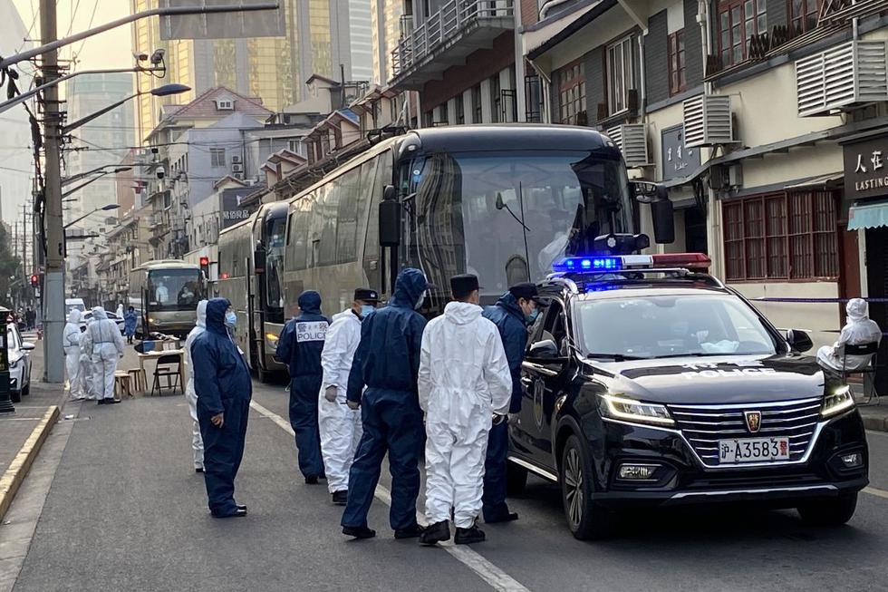 La policía y los trabajadores con trajes de protección se paran junto a los autobuses en un vecindario del que los residentes son evacuados, en el distrito de Huangpu en Shanghái el 21 de enero de 2021. (Texto y foto: AFP).
