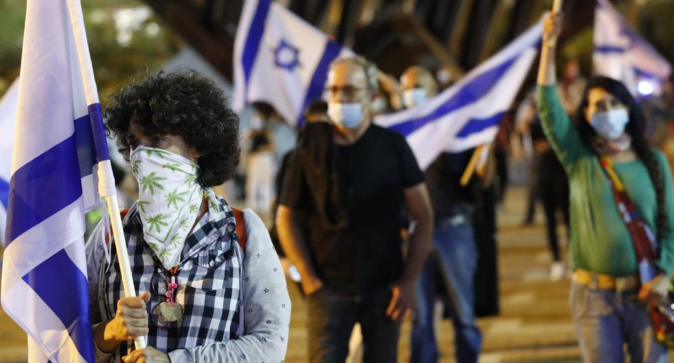 Imagen referencial del 9 de mayo de 2020. Los ciudadanos, con máscaras protectoras y de pie a dos metros de distancia debido a la pandemia del coronavirus, se reúnen en la ciudad costera israelí de Tel Aviv. (JACK GUEZ / AFP).
